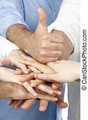 Diverse group of people with their hands together with a thumb up on top