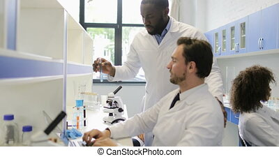 Diverse Group Of Scientists Working In Modern Laboratory,...