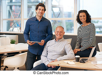 Diverse group of smiling work colleagues in an office
