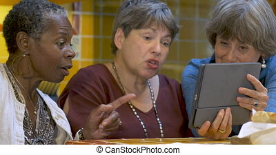 Diverse group of three mature women over 60 using technology...