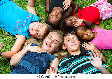 Diverse group og children laying together on grass. - ...
