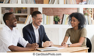 Diverse hr managers laughing listening to african applicant at interview