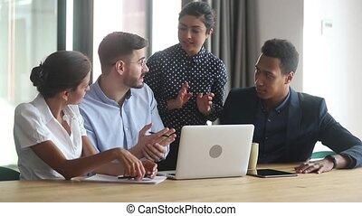 Diverse indian and caucasian mentors teach team discuss...