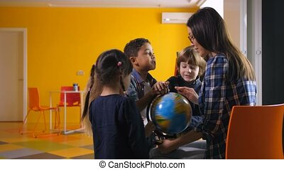 Diverse kids and teacher with globe in kindergarten