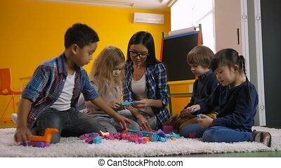Diverse kids playing with constructing toy blocks