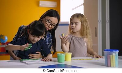 Diverse kids with teacher hand painting in class