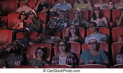 Multi-ethnic groups, couples and individuals in 3d glasses watching film in movie theater. Excited multinational spectators wtching 3d movie, talking, eating popcorn, drinking soda
