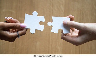 Diverse man and woman hands holding joining pieces connecting puzzle