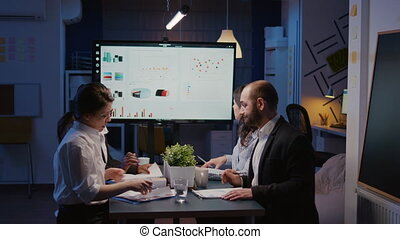 Diverse multi-ethnic group of businesspeople looking at financial presentation on monitor brainstorming company ideas. Teamwork overworking in office meeting room late solving corporate strategy