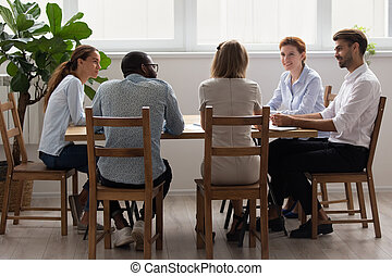 Diverse office business team talking sitting at table in boardroom