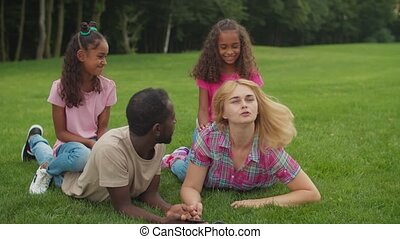 Diverse parents lying on grass with girls on back - ...