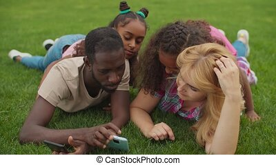 Diverse parents with girls working on smart phone - Positive...