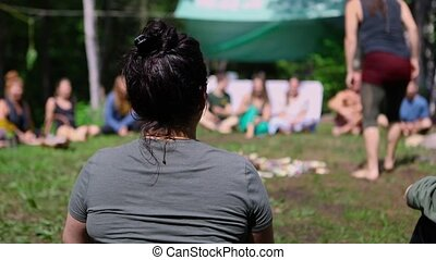 A closeup and rear view on the back of a young woman, sitting in a circle of people around sacred objects during a celebration of native and shamanic cultures.