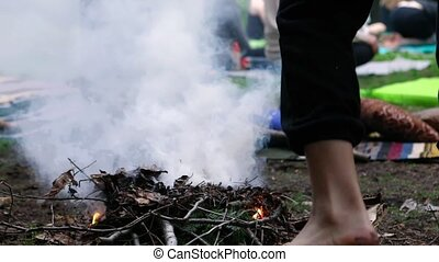 A closeup and slow motion clip of a barefooted person placing kindling on a smoking campfire as blurred people are seen meditating in the background.