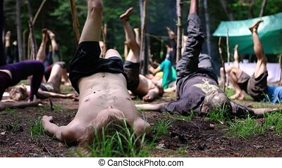 A multiethnic group of people are seen in a forest clearing, experiencing sacred yoga during a nature retreat dedicated to native and shaman cultures, in slow-mo.