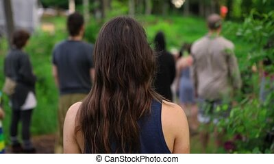A young caucasian girl with long dark hair is seen from behind in slow motion as blurry people are seen in background, practicing native meditation in nature.