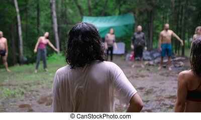 A young woman is seen from the rear, as a mixed group of people practice sacred yoga standing poses in woodland during a multicultural retreat for mind and body.