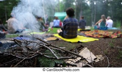 Rising smoke from kindling on a camp fire is seen close up in slow motion, setting the calm atmosphere during a group meditation and yoga session in nature.