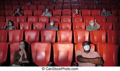 Multinational audience wearing face masks and keeping social distance while watching movie in cinema during epidemic of covid19. Multi-ethnic viewers enjoying movie during pandemic