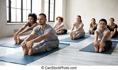 Diverse people practicing yoga with instructor, Seated ...