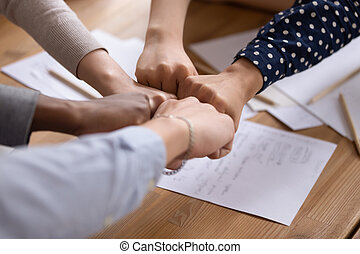 Business partners or group of diverse students put fists in circle fist bump as symbol of engagement in team building, support and synergy, help in cooperation, trust unity in teamwork, close up image