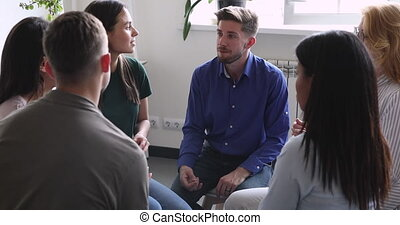 Diverse people sitting in circle, sharing personal problems at psychotherapy session. Male psychologist therapist helping multiracial younger and older patients at group therapy, rehab concept.