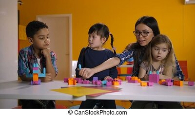 Diverse pupils with teacher enjoying playtime