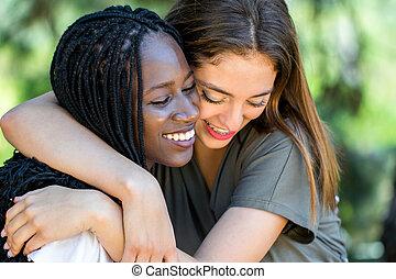 Diverse racial friends embracing outdoors.