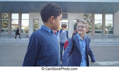 Diverse schoolboys walking holding hands outdoors
