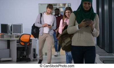 Diverse students browsing cellphones after lecture