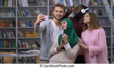 Diverse students taking selfie portrait in library -...