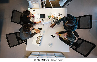Diverse team analyzing data - Overhead view of diverse team...