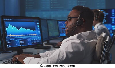 Diverse team of brokers workin in office using workstation and analysis technology. Workplace of professional traders. Global financial markets, business strategy, exchange and banking concepts.