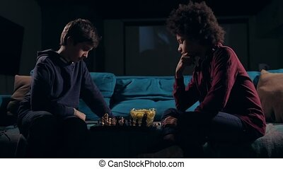 Diverse teen boys moving pieces on chess board - Smart...