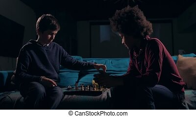 Diverse teen chess players ending game at night - Two clever...
