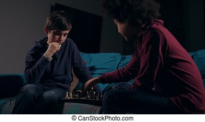 Diverse teen friends playing chess game at home - Two...