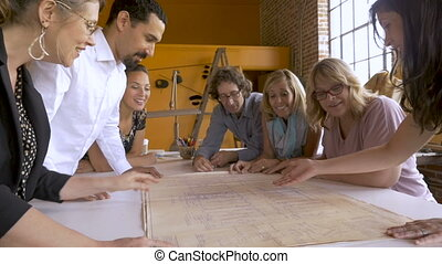 Diverse young attractive millennial mostly women entrepreneurs with their male coworkers pointing at new business blueprints in slow motion