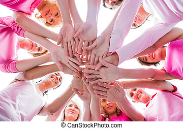 Diverse women smiling in circle wearing pink for breast...