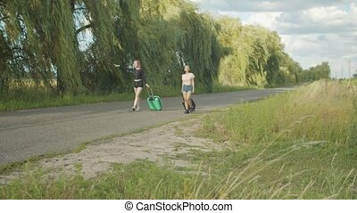 Diverse women travelers hitchhiking on rural road - Positive...