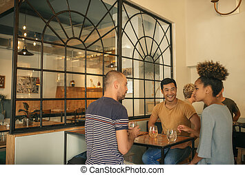 Diverse young friends enjoying drinks together in a bar
