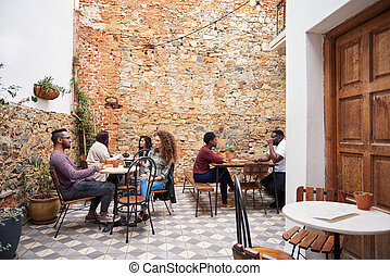 Diverse young people chatting over coffee in a cafe courtyard
