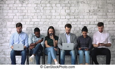 Diverse young people with gadgets, waiting for job interview...