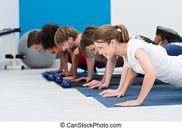 Diverse young people working out in a gym