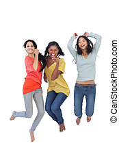 Diverse young women jumping and looking at camera