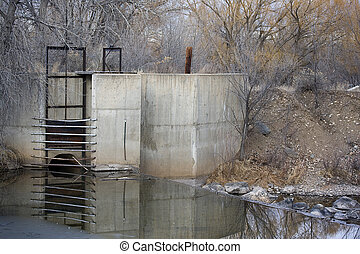 diversion dam and inlet to irrigation ditch, Cache la Poudre River in Colorado, very low water in winter