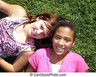 A picture of two young teen girls one black and one white smiling.