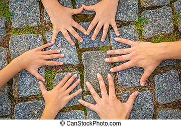 Diversity adult and children hands in circle over paving stone background