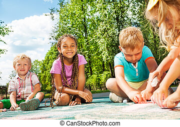 Diversity looking kids draw with chalk