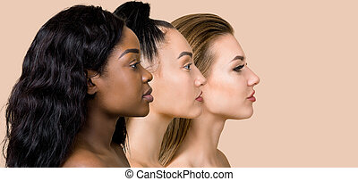 Diversity, multi-ethnic beauty concept. Three beautiful ladies of different races, African, Asian and Caucasian, with natural makeup, posing on the beige studio background in profile, standing in row