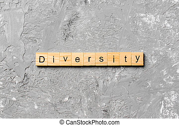 Diversity word written on wood block. Diversity text on cement table for your desing, concept